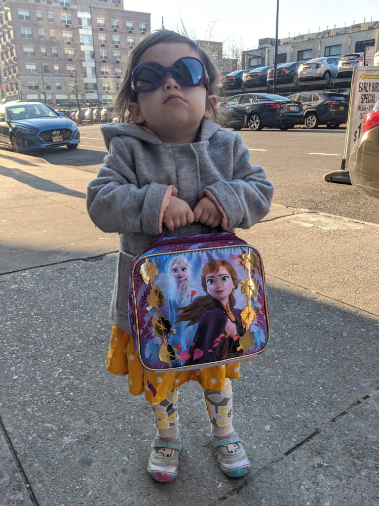 Zelda looking absolutely like a mean boss gripping her Frozen lunchbox and wearing oversized sunglasses